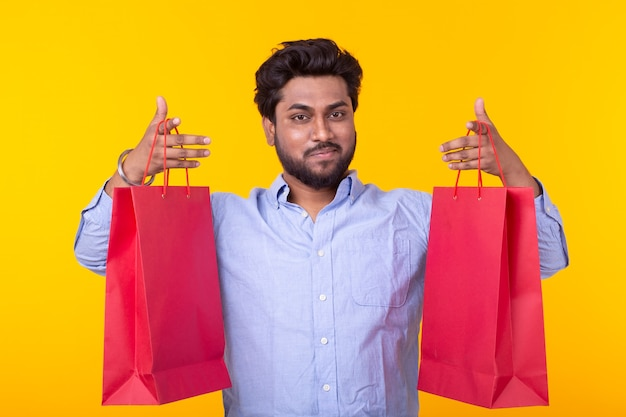Freudiger junger hipster hält rote einkaufstaschen an einer gelben wand. das konzept des einkaufens im supermarkt und geschenke.