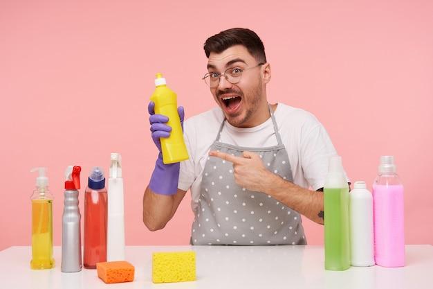 Freudiger junger hübscher brünetter mann in den gläsern, die mit zeigefinger auf flasche waschmittel in der erhobenen hand zeigen und emotional schauen, lokalisiert auf rosa