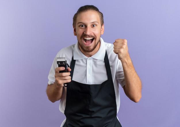 Freudiger junger hübscher friseur, der uniform hält, die haarschneidemaschinen und geballte faust hält, die auf purpur lokalisiert werden