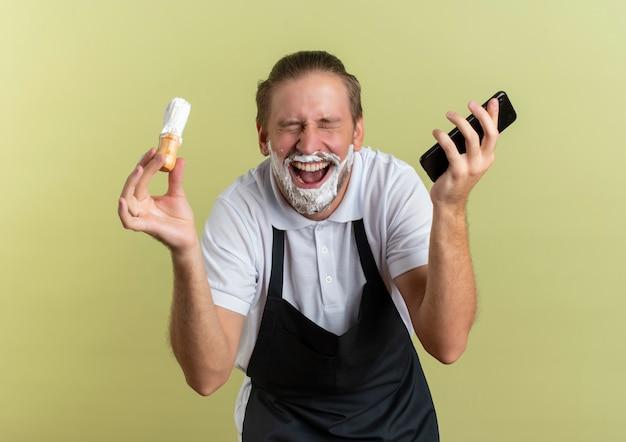 Freudiger junger hübscher friseur, der uniform hält, die handy und rasierpinsel mit geschlossenen augen und mit rasierschaum auf seinem bart trägt, der auf olivgrün isoliert wird