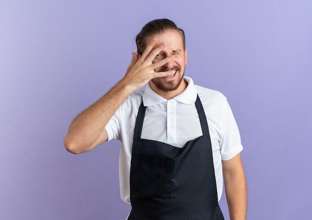 Freudiger junger hübscher friseur, der uniform trägt, die hand auf gesicht setzt, das durch finger schaut und an front, die auf lila isoliert ist, zwinkert