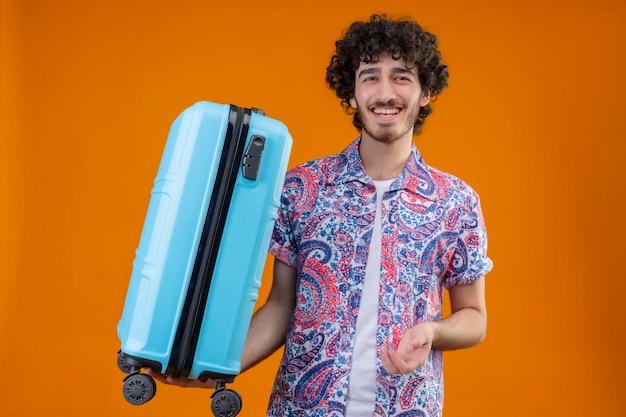 Freudiger junger hübscher gelockter reisender mann, der koffer auf lokalisiertem orange raum hält