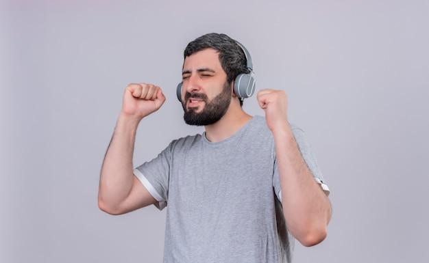 Freudiger junger hübscher kaukasischer mann, der kopfhörer trägt, die musik mit geschlossenen augen und erhobenen fäusten hören, die auf weiß isoliert werden