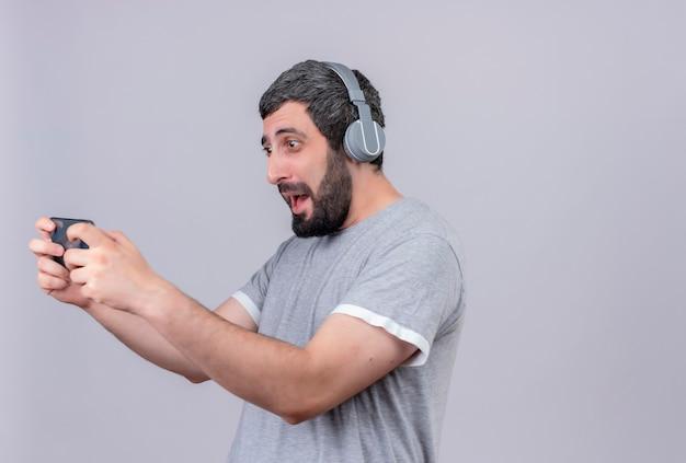 Freudiger junger hübscher kaukasischer mann, der kopfhörer unter verwendung seines auf weiß lokalisierten handys trägt