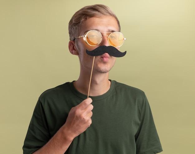 Freudiger junger hübscher kerl, der grünes hemd mit brille trägt, die falschen schnurrbart auf stock lokalisiert auf olivgrüner wand hält