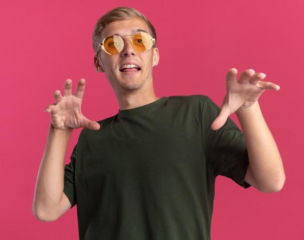 Freudiger junger hübscher kerl, der grünes hemd und brille trägt, die tigerartgeste, die auf rosa wand lokalisiert zeigt