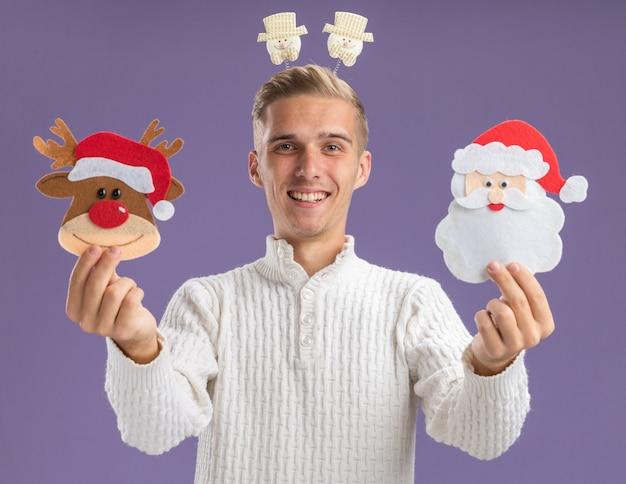 Freudiger junger hübscher kerl, der schneemann-stirnband trägt, das weihnachtspapierverzierungen in richtung kamera ausdehnt, die kamera lokalisiert auf lila hintergrund betrachtet