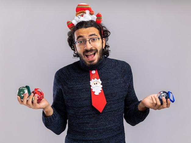 Freudiger junger hübscher kerl, der weihnachtskrawatte mit haarreifen hält, der weihnachtskugeln lokalisiert auf weißem hintergrund hält
