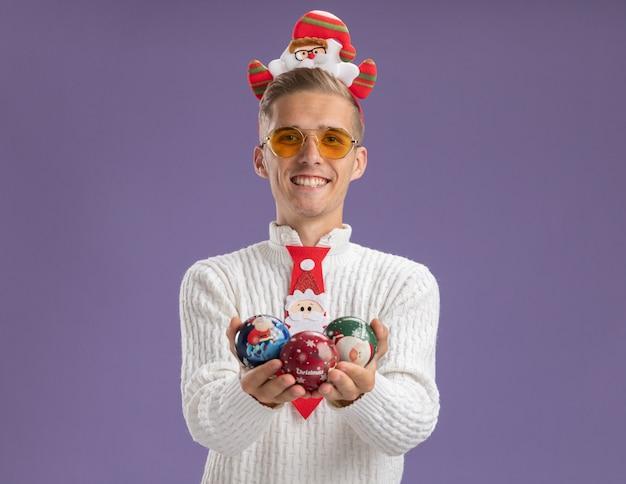 Freudiger junger hübscher kerl, der weihnachtsmann-stirnband und krawatte mit brille trägt, die weihnachtsballverzierungen hält, die kamera lokalisiert auf lila hintergrund betrachten