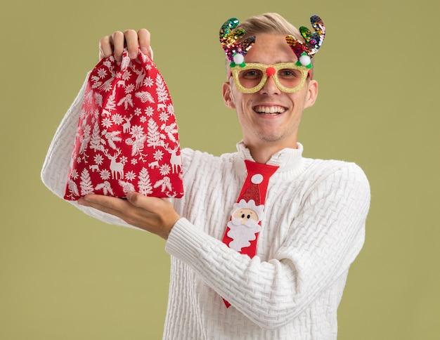 Freudiger junger hübscher kerl, der weihnachtsneuheitsgläser und weihnachtsmannkrawatte trägt, die weihnachtssack lokalisiert auf olivgrüner wand hält