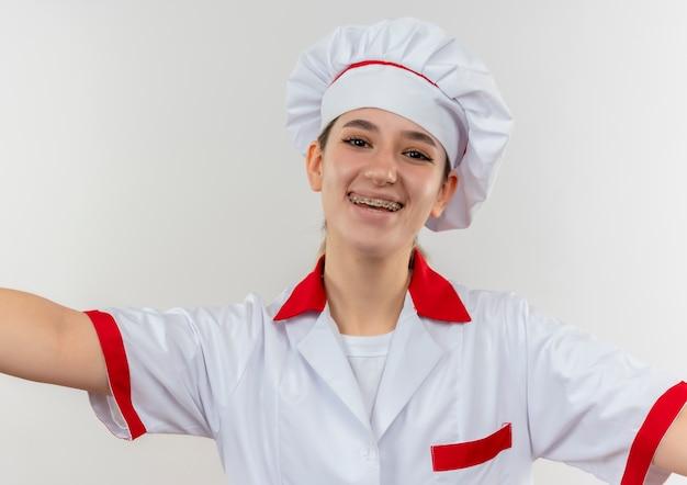 Freudiger junger hübscher koch in der kochuniform mit zahnspangen, die mit offenen armen lokalisiert auf weißem raum suchen