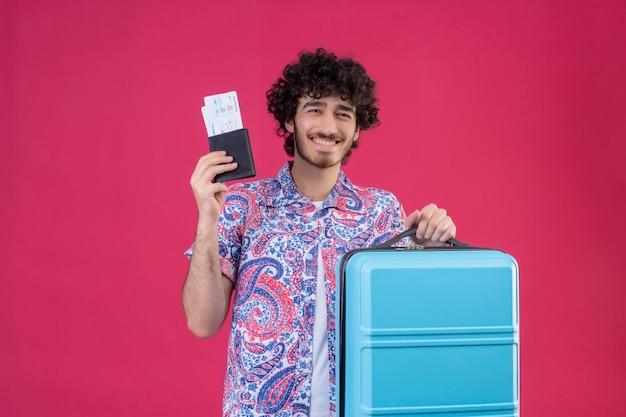 Freudiger junger hübscher lockiger reisender mann, der brieftasche und flugtickets und koffer auf lokalisiertem rosa raum mit kopienraum hält