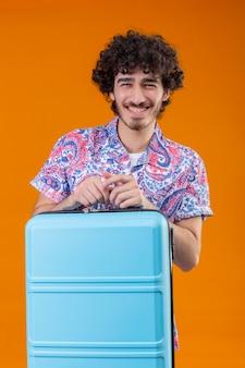 Freudiger junger hübscher lockiger reisender mann, der hände auf koffer auf lokalisiertem orange raum setzt