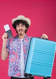 Freudiger junger hübscher lockiger reisender mann, der hut hält, der brieftasche und flugtickets und koffer auf lokalisiertem rosa raum hält