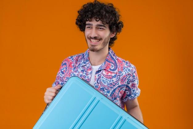 Freudiger junger hübscher lockiger reisender mann, der koffer auf lokalisiertem orange raum mit kopienraum hält