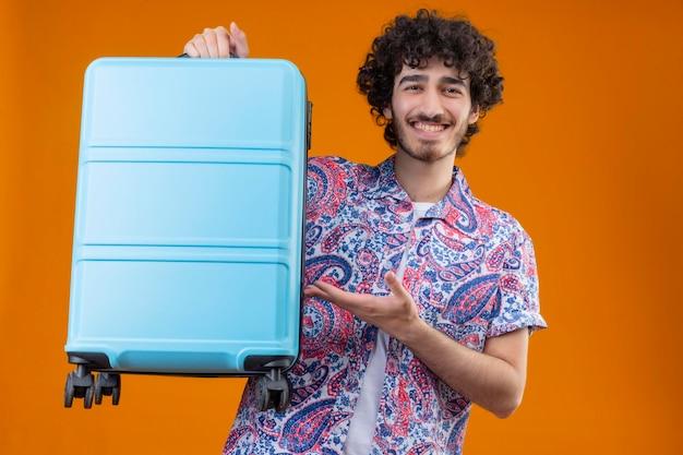Freudiger junger hübscher lockiger reisender mann, der koffer erhebt und mit der hand auf ihn auf lokalisiertem orangefarbenem raum zeigt