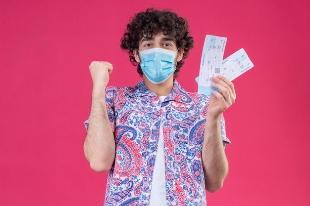 Freudiger junger hübscher lockiger reisender mann, der medizinische maske trägt, die flugtickets mit erhabener faust auf lokalisiertem rosa raum mit kopienraum hält