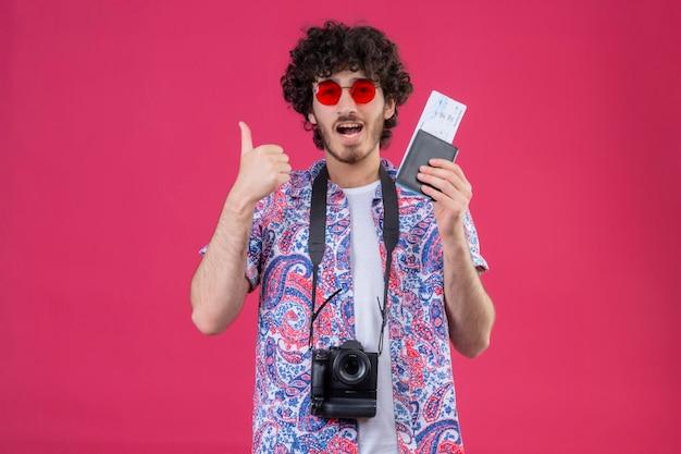 Freudiger junger hübscher lockiger reisender mann, der sonnenbrille hält, die brieftasche und flugtickets mit kamera um hals hält, zeigt daumen oben auf isoliertem rosa raum mit kopienraum