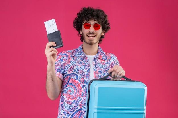 Freudiger junger hübscher lockiger reisender mann, der sonnenbrillen hält, die brieftasche und flugtickets mit koffer auf lokalisiertem rosa raum mit kopienraum halten