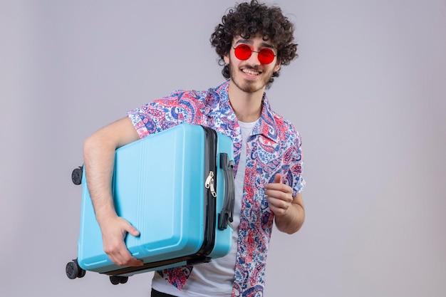 Freudiger junger hübscher lockiger reisender mann, der sonnenbrillen hält, die koffer auf lokalisiertem weißem raum mit kopienraum halten