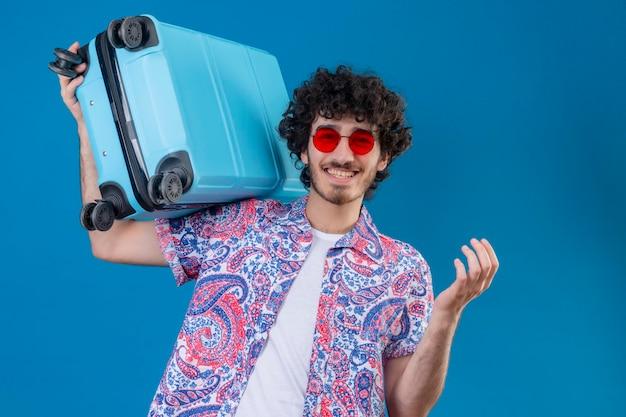 Freudiger junger hübscher lockiger reisender mann, der sonnenbrillen hält, die koffer auf schulter auf lokalisiertem blauem raum mit kopienraum halten