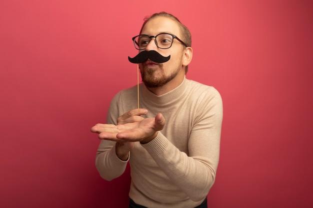 Freudiger junger hübscher mann im beige rollkragenpullover und in den gläsern, die lustigen schnurrbart auf stock halten, der einen kuss bläst