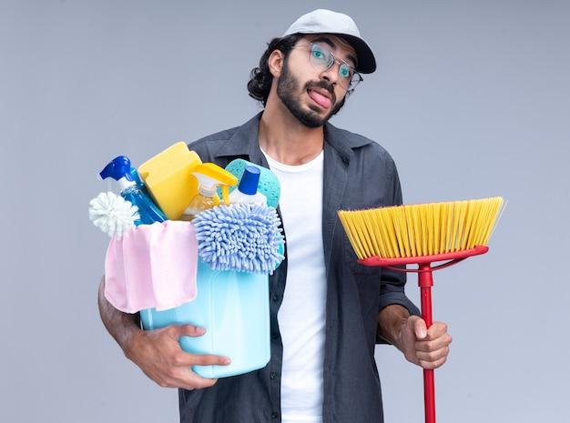 Freudiger junger hübscher reinigungsmann, der t-shirt und kappe hält, die eimer mit reinigungswerkzeugen hält, die zunge mit mopp lokalisiert auf weißer wand zeigen