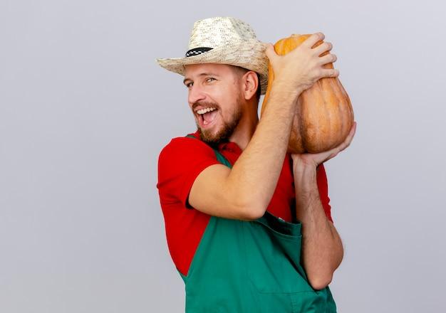 Freudiger junger hübscher slawischer gärtner in der uniform und im hut, die butternusskürbis nahe kopf halten, der lokal schaut