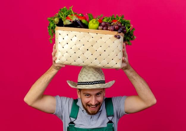 Freudiger junger hübscher slawischer gärtner in der uniform und im hut, die korb des gemüses über kopf lokalisiert auf purpurroter wand halten