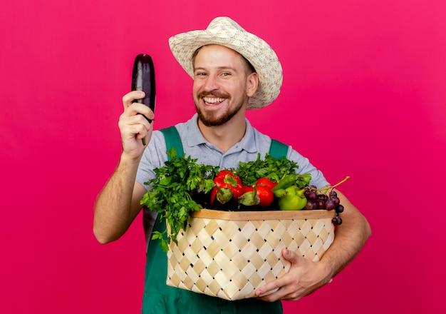 Freudiger junger hübscher slawischer gärtner in der uniform und im hut, die korb des gemüses und der aubergine halten, lokalisiert auf purpurroter wand