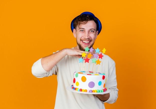 Freudiger junger hübscher slawischer party-typ, der partyhut hält, der geburtstagstorte mit sternen betrachtet, die kamera betrachten, die hand unter kinn lokalisiert auf orange hintergrund mit kopienraum hält