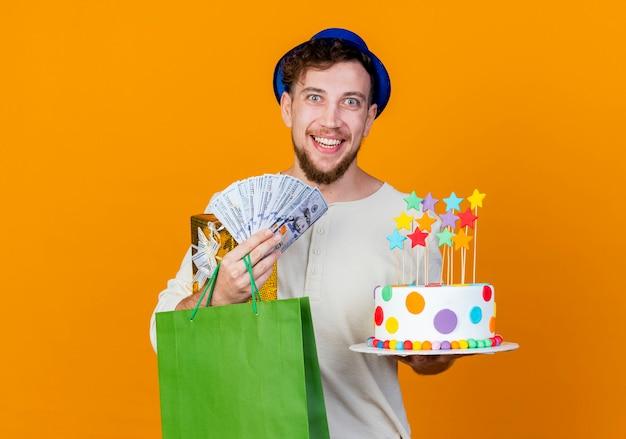 Freudiger junger hübscher slawischer party-typ, der partyhut hält, der geschenkbox-geldpapiertüte und geburtstagstorte mit sternen hält, die kamera lokalisiert auf orange hintergrund mit kopienraum betrachten