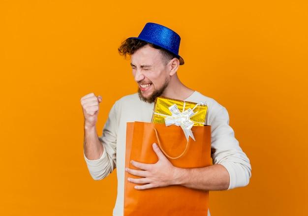Freudiger junger hübscher slawischer party-typ, der partyhut hält, der geschenkboxen in der papiertüte tut, die ja geste lokalisiert auf orange hintergrund mit kopienraum tut