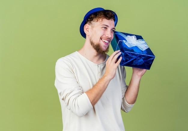 Freudiger junger hübscher slawischer party-typ, der partyhut trägt, der gerade geschenkbox lokalisiert auf olivgrünem hintergrund mit kopienraum sucht