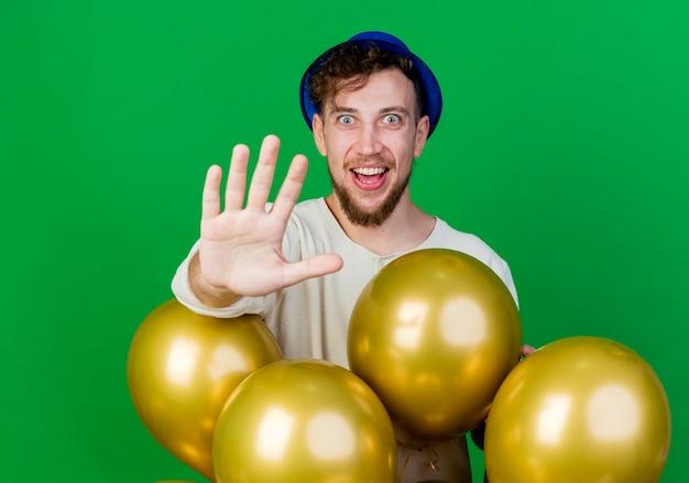 Freudiger junger hübscher slawischer party-typ, der partyhut trägt, der hinter luftballons steht, die kamera betrachten, die hand in richtung kamera lokalisiert auf grünem hintergrund ausdehnt