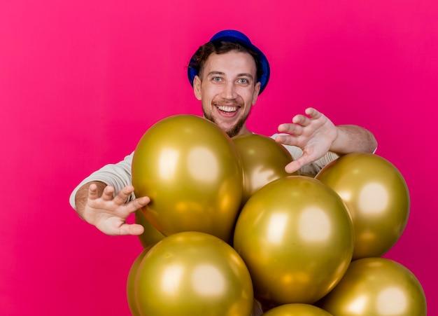 Freudiger junger hübscher slawischer party-typ, der partyhut trägt, der hinter luftballons steht und kamera betrachtet, die leere hände lokalisiert auf purpurrotem hintergrund zeigt