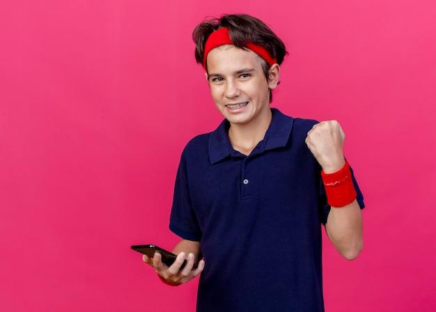 Freudiger junger hübscher sportlicher junge, der stirnband und armbänder mit zahnspangen hält, die handy halten, das vorne schaut, ja geste lokalisiert auf rosa wand mit kopienraum