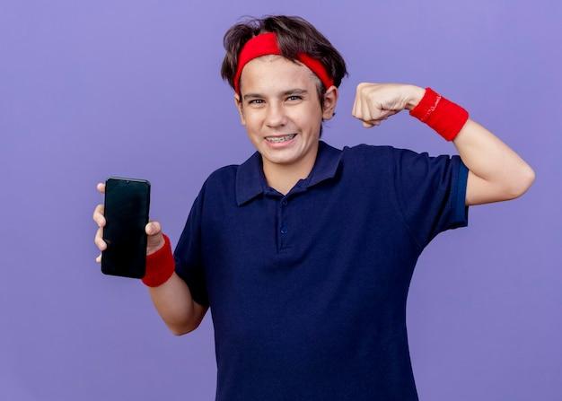 Freudiger junger hübscher sportlicher junge, der stirnband und armbänder mit zahnspangen trägt, die handy zeigen, das starke geste tut, die an der front lokalisiert auf lila wand betrachtet