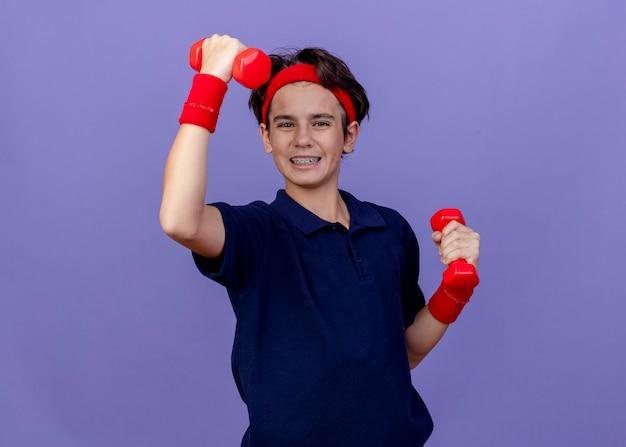 Freudiger junger hübscher sportlicher junge, der stirnband und armbänder mit zahnspangen trägt, die hantel, die auf lila wand mit kopierraum lokalisiert aufhebt