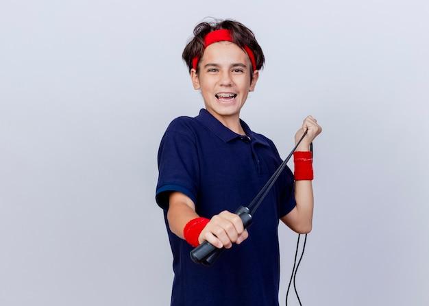 Freudiger junger hübscher sportlicher junge, der stirnband und armbänder mit zahnspangen trägt, die kamera ziehen springseil lokalisiert auf weißem hintergrund mit kopienraum betrachten