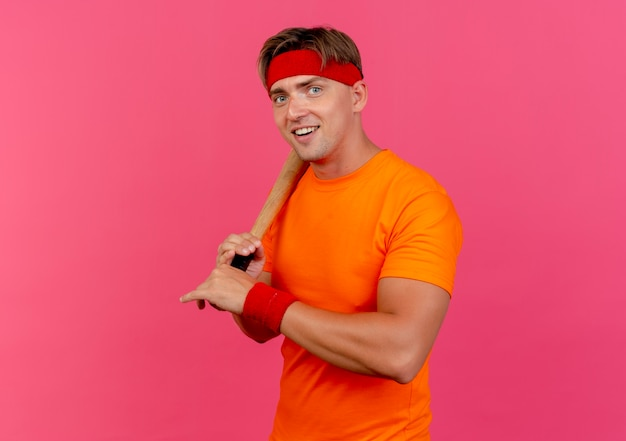 Freudiger junger hübscher sportlicher mann, der stirnband und armbänder hält, die baseballschläger auf schulter lokalisiert auf rosa halten