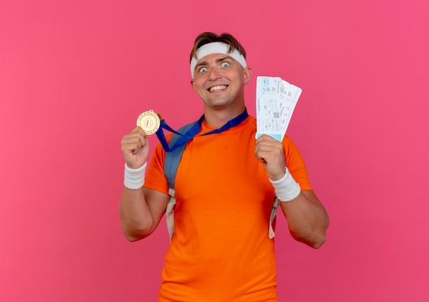 Freudiger junger hübscher sportlicher mann, der stirnband und armbänder und rückentasche mit medaille um hals hält, die flugtickets und medaille lokalisiert auf rosa hält