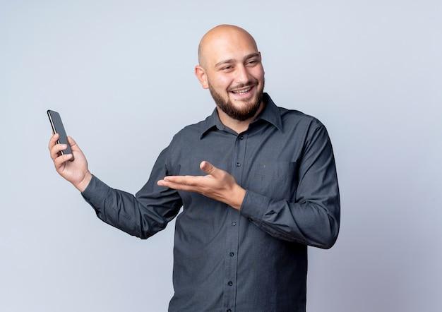 Freudiger junger kahler callcenter-mann, der handy hält, das seite betrachtet und leere hand lokalisiert auf weiß zeigt