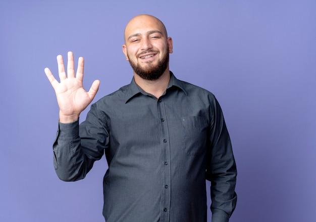 Freudiger junger kahlköpfiger callcenter-mann, der fünf mit der hand zeigt, die auf purpur lokalisiert wird