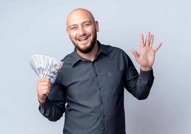 Freudiger junger kahlköpfiger callcenter-mann, der geld hält und fünf mit der hand lokalisiert auf weiß zeigt