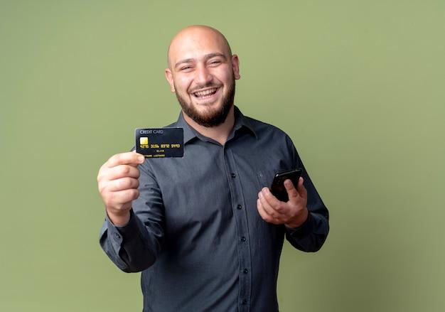 Freudiger junger kahlköpfiger callcenter-mann, der handy hält und kreditkarte streckt, die auf olivgrün isoliert wird