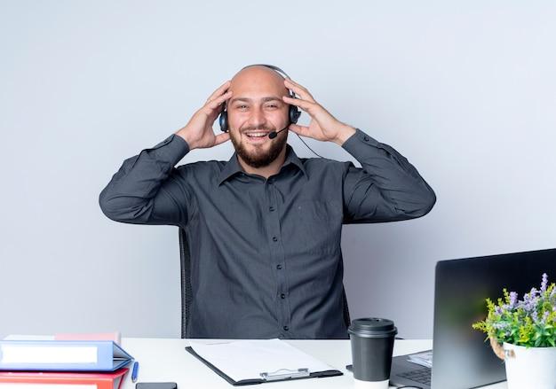 Freudiger junger kahlköpfiger callcenter-mann, der headset trägt, das am schreibtisch mit arbeitswerkzeugen sitzt, die hände auf headset lokalisiert auf weiß setzen