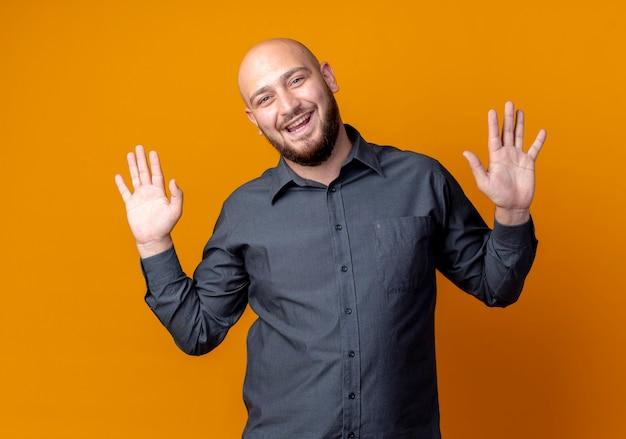 Freudiger junger kahlköpfiger callcenter-mann, der leere hände lokalisiert auf orange zeigt