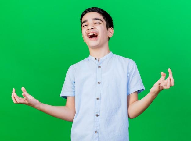 Freudiger junger kaukasischer junge, der kamera betrachtet, die leere hände lokalisiert auf grünem hintergrund zeigt