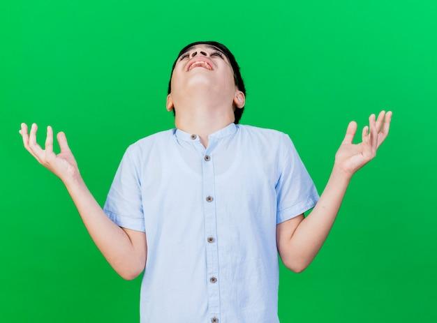Freudiger junger kaukasischer junge, der nach oben schaut, hält hände in der luft und dankt gott isoliert auf grünem hintergrund